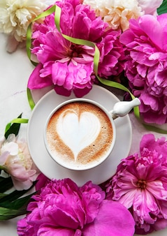 Rosa pfingstrose und tasse kaffee im schönen stil auf weißem marmorhintergrund. blumiger hintergrund. draufsicht