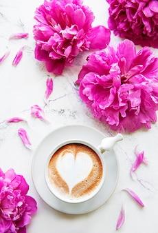 Rosa pfingstrose und tasse kaffee im schönen stil auf weißem marmortisch.