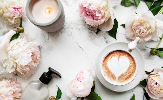 Rosa pfingstrose und tasse kaffee im schönen stil auf weißer oberfläche