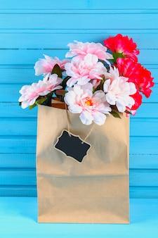 Rosa pfingstrosen in einem handwerkspaket mit einer tafel auf einem blauen holztisch. postkarte für den urlaub.