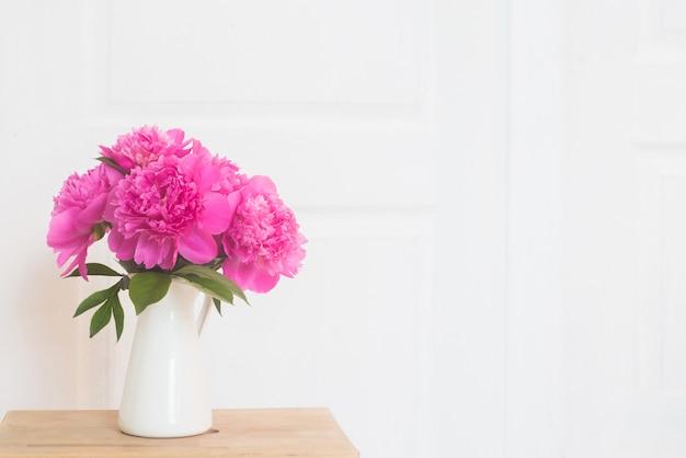 Rosa pfingstrosen in weißer emaillierter vase. blumenstrauß auf holztisch im innenraum der weißen provence. wohnraum mit dekorelementen