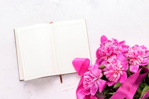 Rosa pfingstrosen und ein offenes tagebuch auf einem hellen stein