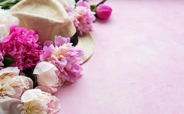 Rosa pfingstrosen und hut auf einem rosa konkreten hintergrund