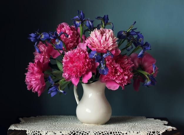 Rosa pfingstrosen und iris in einem weißen krug. stillleben mit einem blumenstrauß von gartenblumen auf dem tisch.