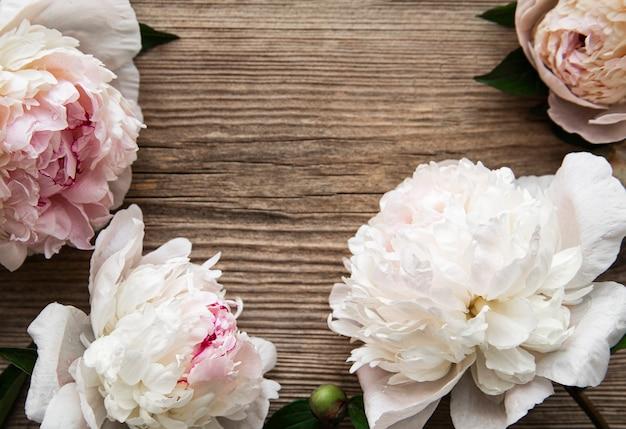 Rosa pfingstrosenblüten als bordüre auf einem alten holzhintergrund
