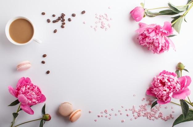 Rosa pfingstrosenblumen und ein tasse kaffee auf weiß