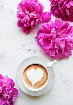 Rosa pfingstrosenblumen und eine tasse kaffee