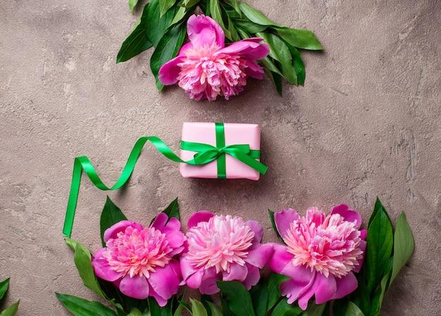 Rosa pfingstrosenblumen und geschenkbox