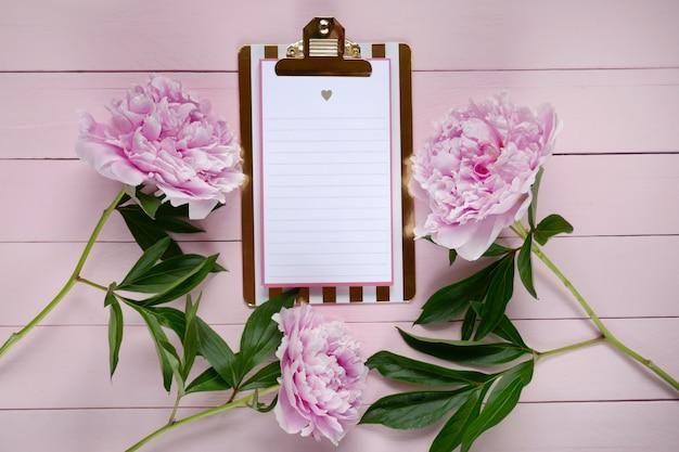 Rosa pfingstrosenblumen und leeres klemmbrett auf rosa bretthintergrund