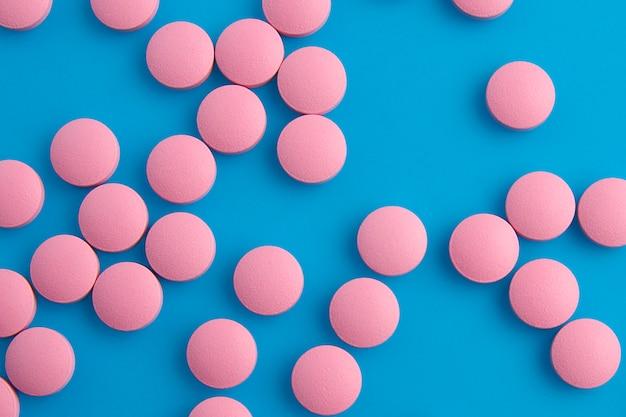 Rosa pillen auf draufsicht des blauen hintergrundes