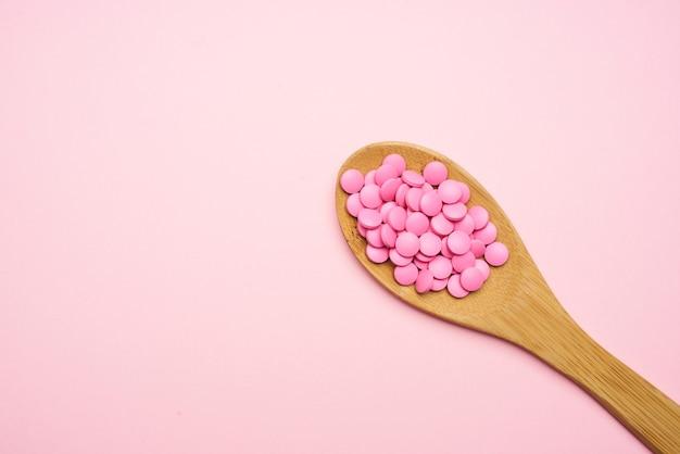Rosa pillen im löffel isolierte hintergrundmedizinapotheke