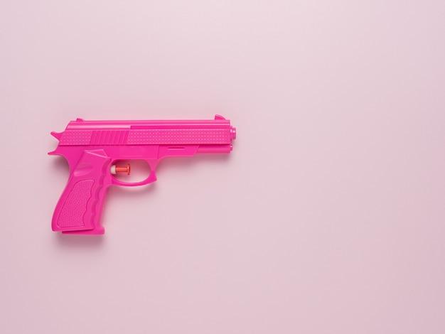 Rosa pistole auf rosa pastellhintergrund