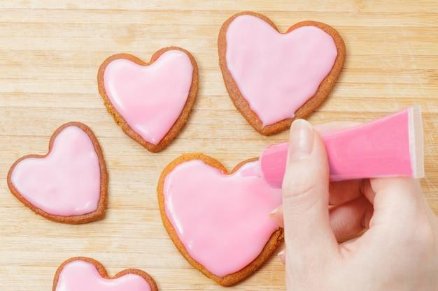 Rosa plätzchen für valentinstag auf hölzernem hintergrund