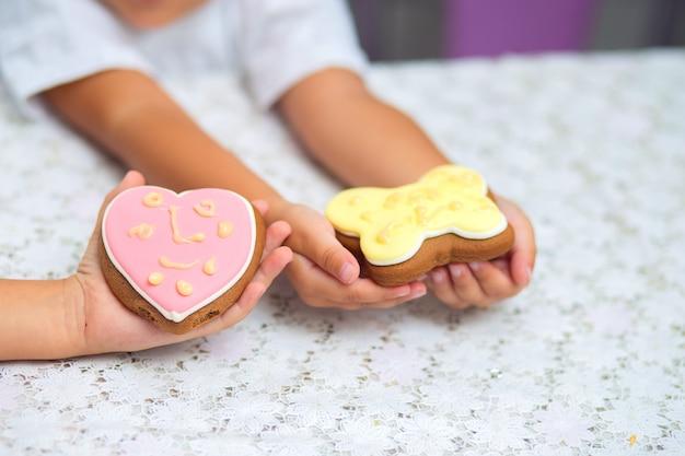 Rosa plätzchen in form eines schmetterlings und eines herzens liegen auf der hand einer kinder