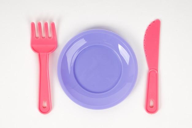 Rosa plastikbabyrosagabel, -messer und -platte lokalisiert