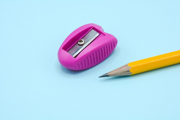 Rosa plastikbleistiftspitzer und ein gelber bleistift auf blauem hintergrund