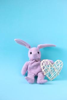Rosa plüschhase sitzt auf blauem hintergrund und hält weißes herz, vertikale ausrichtung. valentinstagskarte