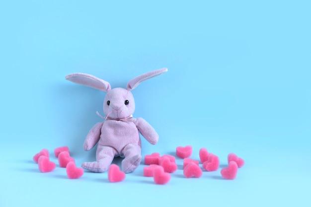 Rosa plüschhase sitzt auf blauem hintergrund unter weichen rosa herzen. valentinstagskarte