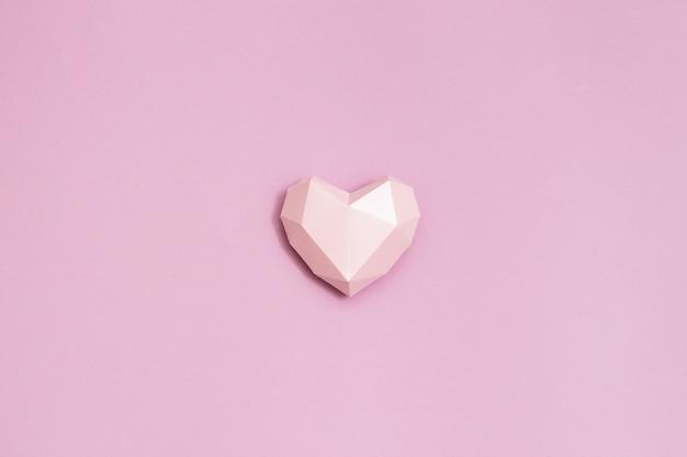 Rosa polygonale papierherzform auf rosa papier. feiertagshintergrund für valentinstag.