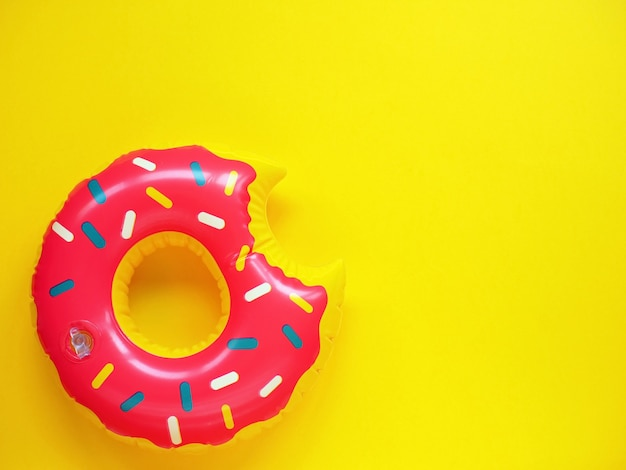 Rosa pool schweben in form von donut auf gelber oberfläche