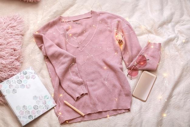 Rosa pullover telefon und rosa kissen liegen auf dem laken