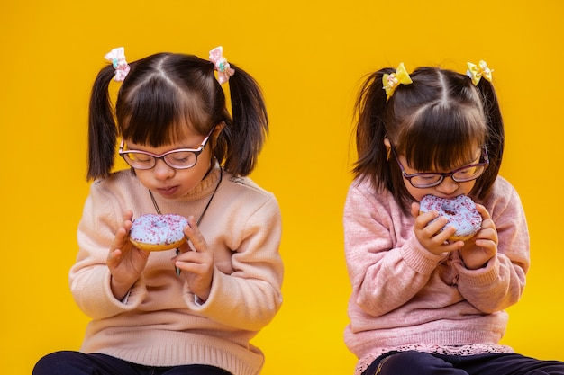 Rosa pullover tragen. konzentrierte junge schwestern mit unordnung, die farbige donuts genießen, während sie sie mit beiden händen tragen