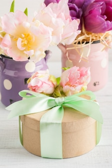 Rosa purpurrote tulpen und geschenkbox mit grünem band