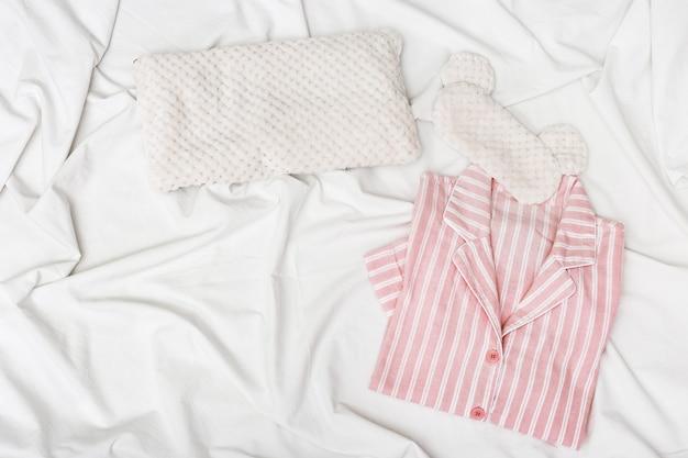 Rosa pyjama, flauschige augenmaske zum schlafen und weiches kissen auf dem bett mit weißem baumwolltuch