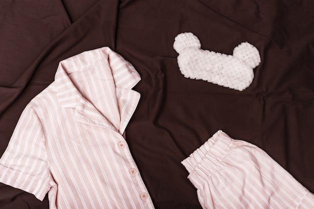 Rosa pyjama für mädchen, lustige und flauschige augenmaske zum schlafen auf schokoladenfarbenem blatt.