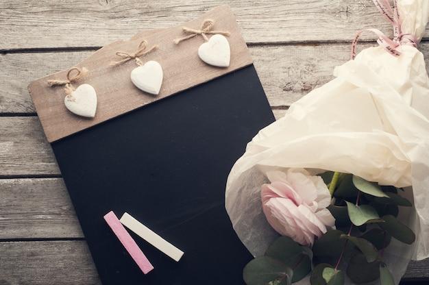 Rosa ranunculus und tafel mit kreide