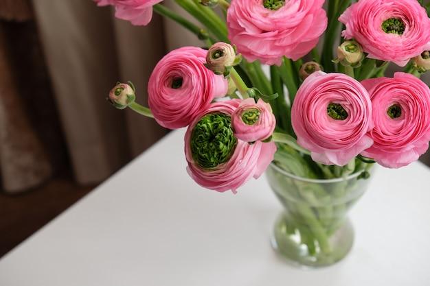 Rosa ranunculusblumenstrauß im transparenten glasvase auf weißer tabelle.