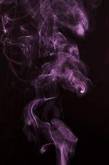 Rosa rauchmuster ausgebreitet über schwarzem hintergrund