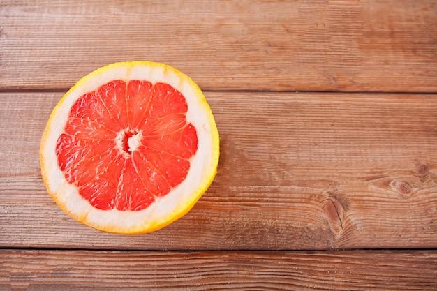 Rosa reife grapefruitscheibe auf dem holztisch.