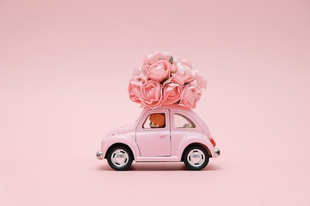 Rosa retro- spielzeugauto, das blumenstrauß von blumen liefert