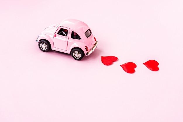 Rosa retro- spielzeugauto, das handwerksherz für valentinstag liefert