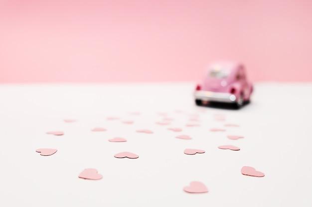 Rosa retro- spielzeugauto, das herzen auf rosa hintergrund liefert. valentinstagskarte