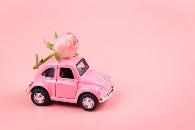 Rosa retro-spielzeugauto liefert eine blume auf einer rosa oberfläche