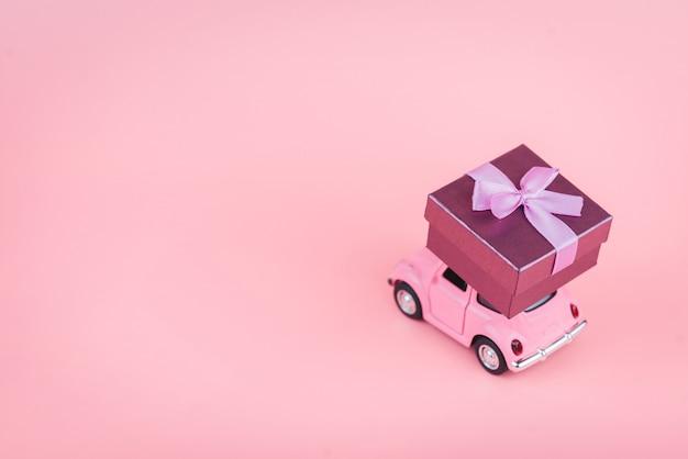 Rosa retro-spielzeugauto liefert eine geschenkbox auf einer rosa oberfläche
