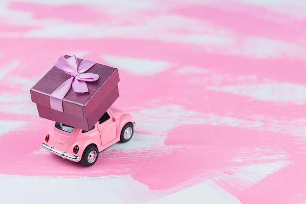 Rosa retro-spielzeugauto liefert eine geschenkbox auf rosa hintergrund. 14. februar postkarte, valentinstag. blumenlieferung. frauentag