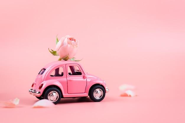 Rosa retro-spielzeugauto liefert eine rosa blume auf rosa hintergrund. 14. februar postkarte, valentinstag. 8. märz, internationaler frauentag