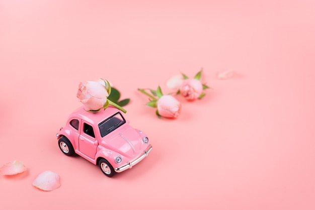 Rosa retro-spielzeugauto liefert eine rosa blume auf rosa hintergrund.