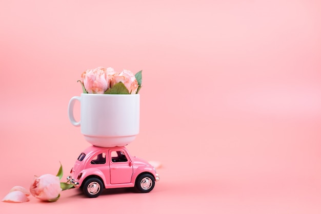 Rosa retro-spielzeugauto liefert eine weiße tasse mit blumen auf rosa hintergrund. muttertag