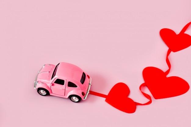 Rosa retro-spielzeugauto mit roten herzen