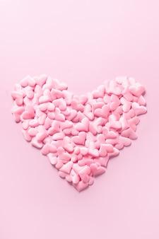Rosa romantisches herz auf rosa hintergrund. vertikale monochrome gruß-valentinstagskarte. liebeskonzept.