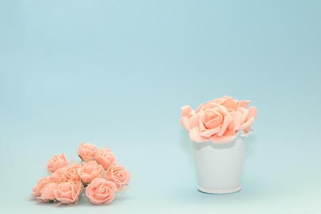 Rosa rosafarbene blumenblätter in einem weißen spielzeugeimer nahe bei blumen auf einem hellblauen hintergrund