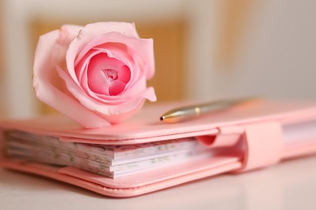Rosa rose auf einem geschlossenen notizbuch romantik und zarte pastellfarben für eine hochzeitsfeier oder die geburt eines mädchens