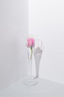 Rosa rose in einem glas mit leicht ausgeprägten regenbogenfarben in der ecke. sanftes sommerfrühlingskonzept mit sanften pastellfarben