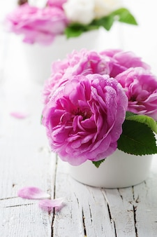 Rosa rosen auf dem holztisch