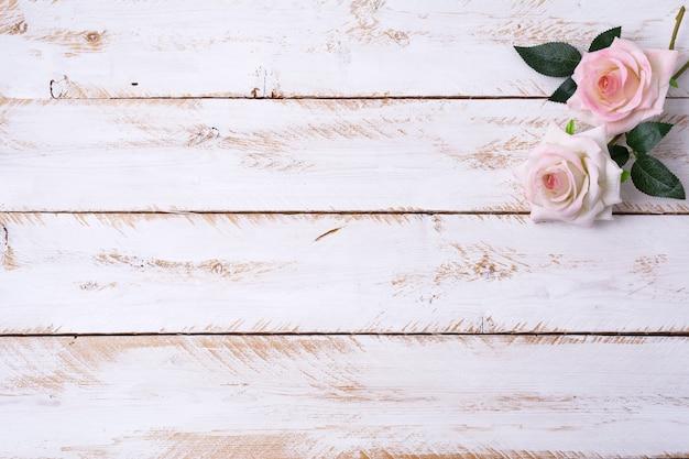 Rosa rosen auf dem weiß gestrichenen holztisch