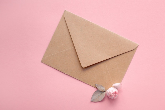 Rosa rosen auf einem umschlag aus kraftpapier auf einem blassrosa hintergrund